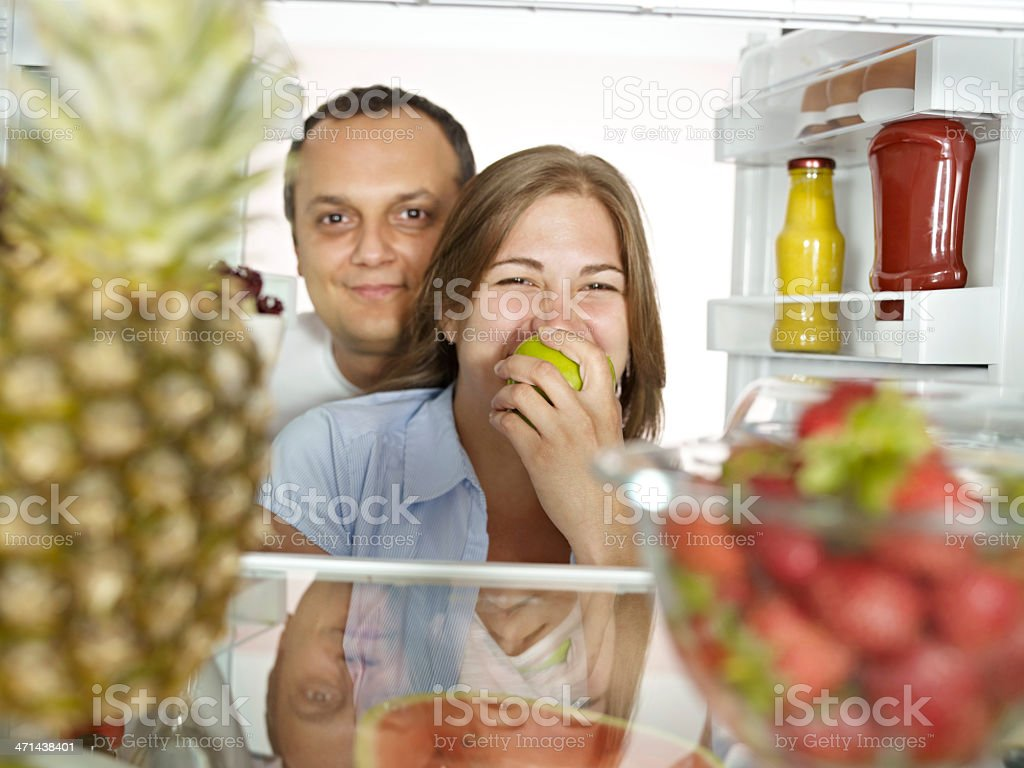 Couple Looking At Camera From Refrigerator royalty-free stock photo