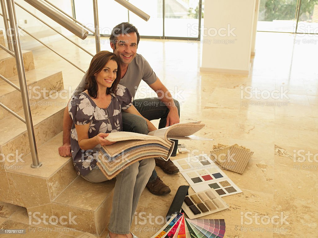 Couple looking at carpet samples in empty house royalty-free stock photo