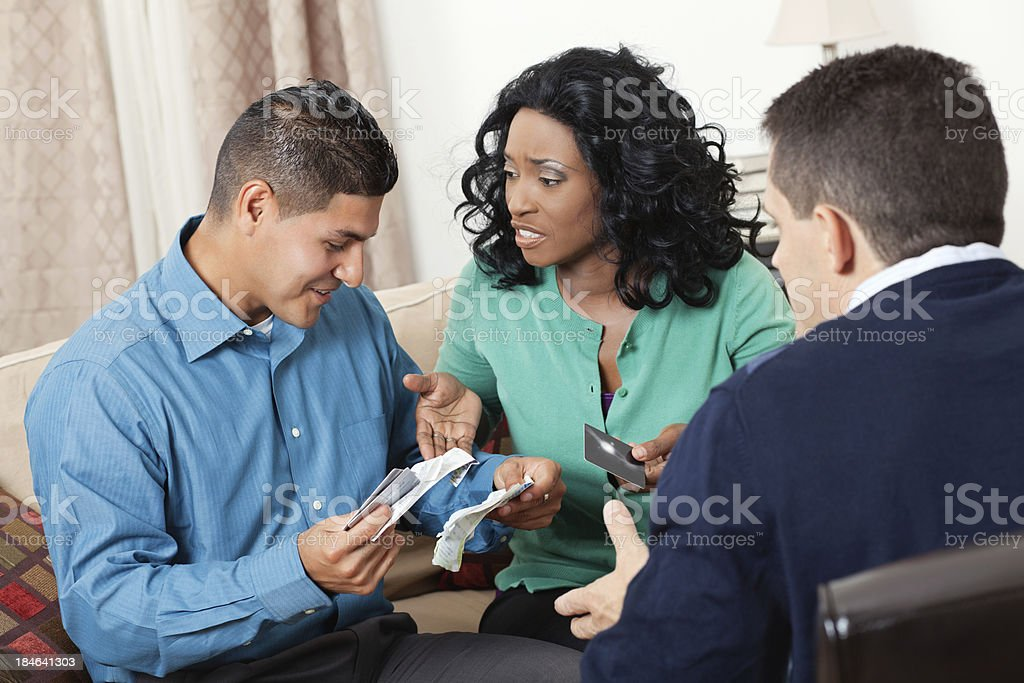 Couple looking at credit card bills with financial advisor royalty-free stock photo