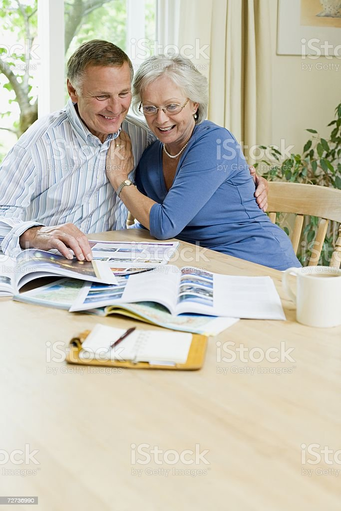 Couple looking at holiday brochures stock photo