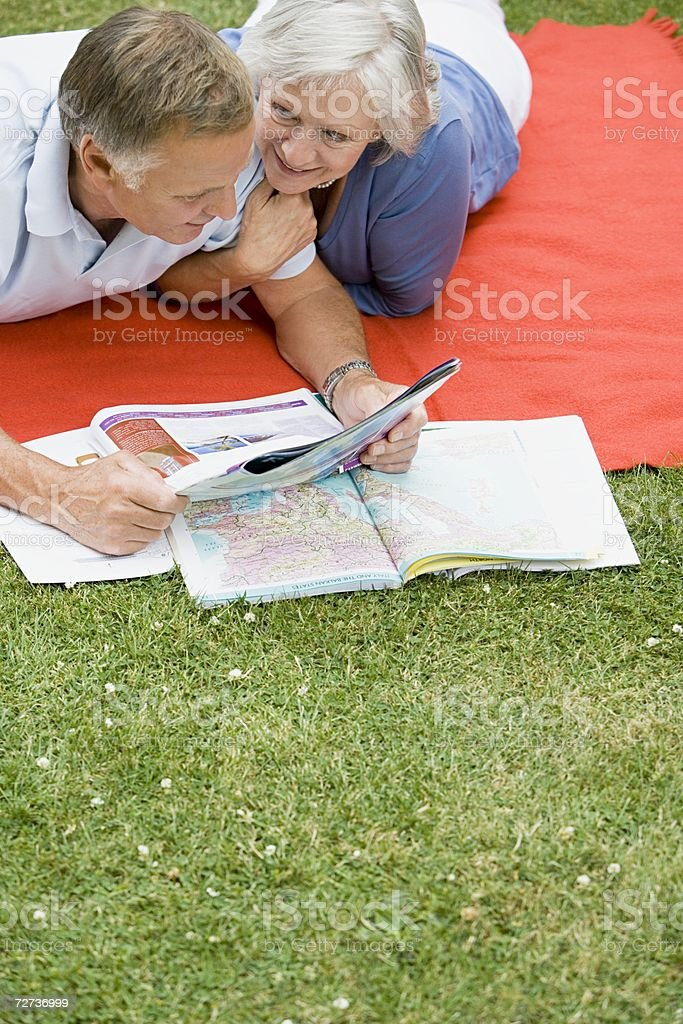 Couple looking at map and holiday brochure royalty-free stock photo