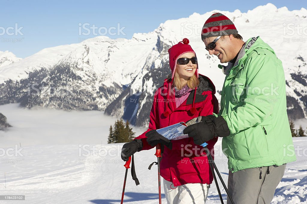Couple Looking At Map Whilst On Ski Holiday In Mountains stock photo