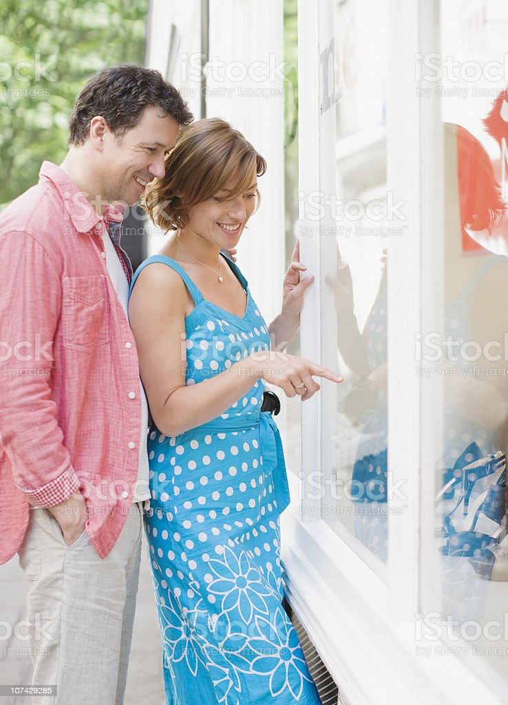 Couple looking at merchandise in store window together royalty-free stock photo