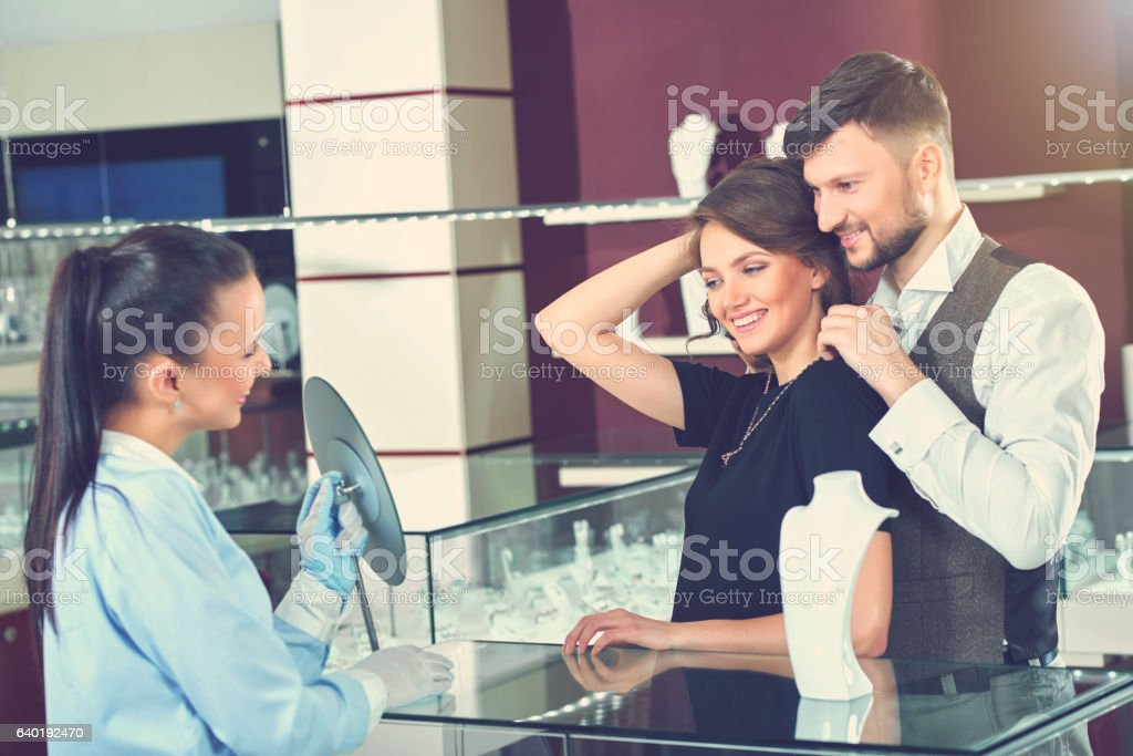 Couple looking at mirror when man trying necklace. stock photo