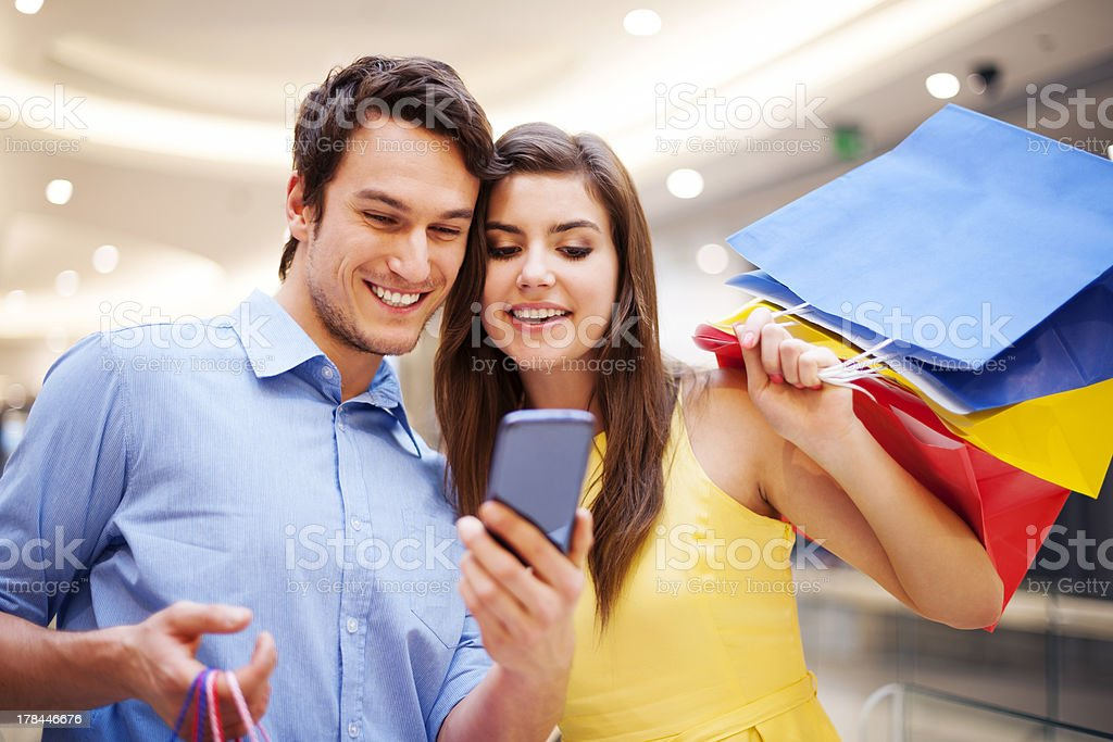 Couple looking at mobile phone while shopping stock photo