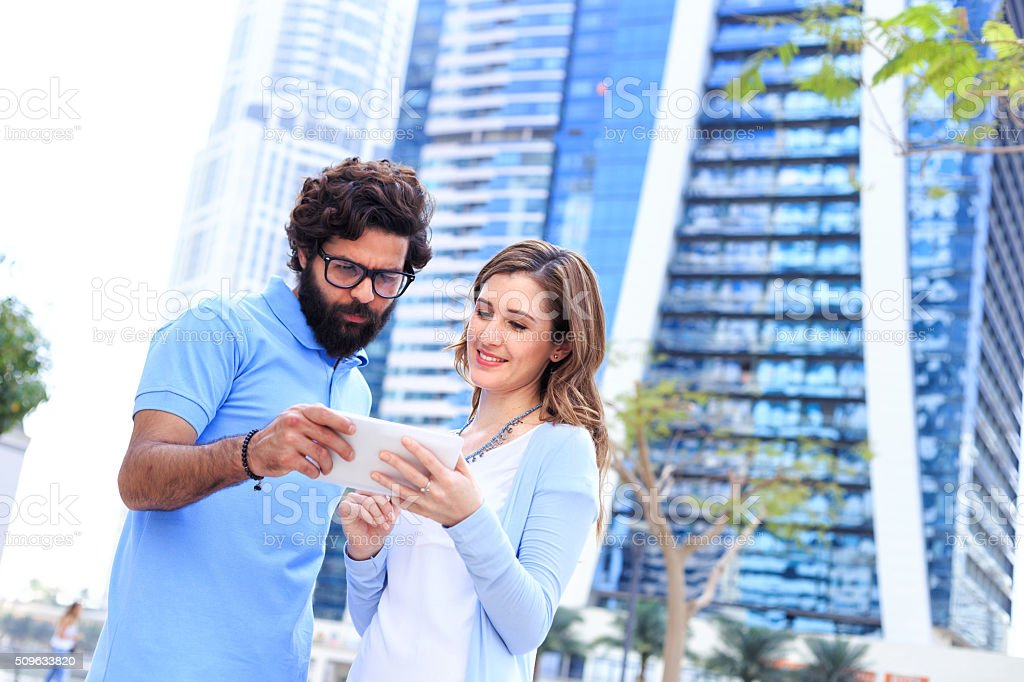 Couple looking at phone for direction - Dubai stock photo