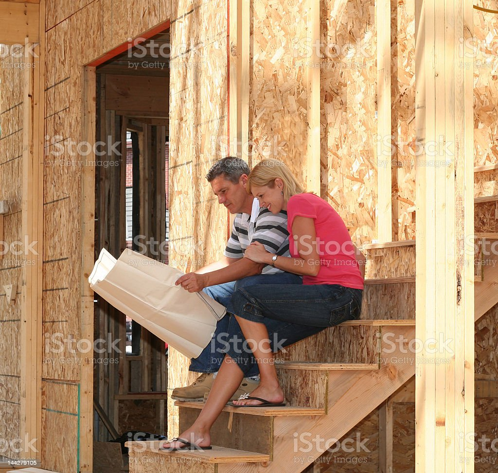 A couple looking at plans and building a new house together stock photo