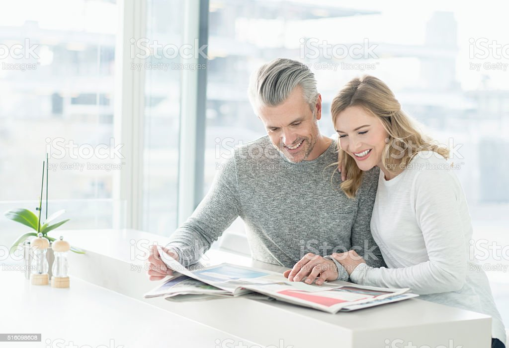 Couple looking at the newspaper at home stock photo