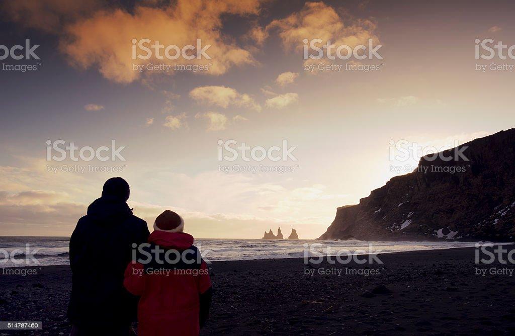 Couple looking at the Reynisdrangar basalt sea stacks , Vik,Iceland stock photo
