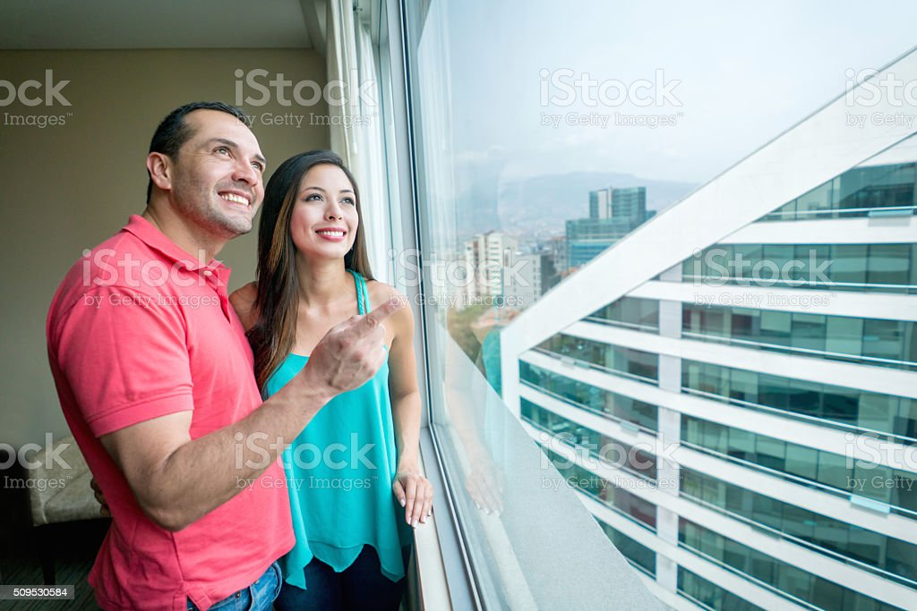 Couple looking at the view on their hotel room stock photo