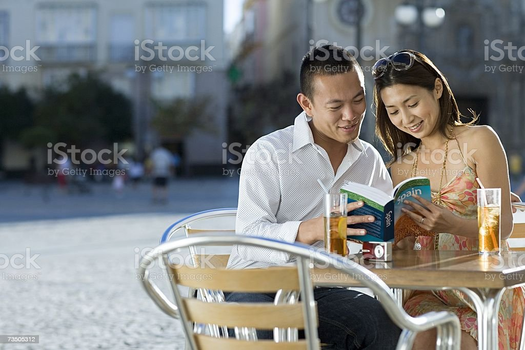 Couple looking at tour guide royalty-free stock photo