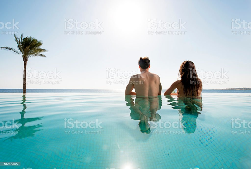 Couple looking at view from infinity pool. stock photo
