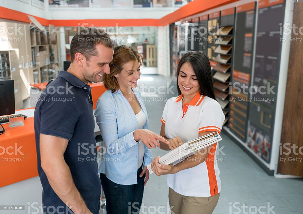 Couple looking at wood samples at a furniture store stock photo