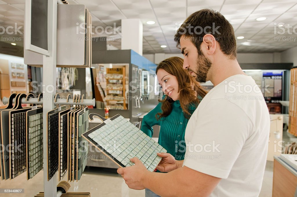 couple looking bathroom tiles stock photo