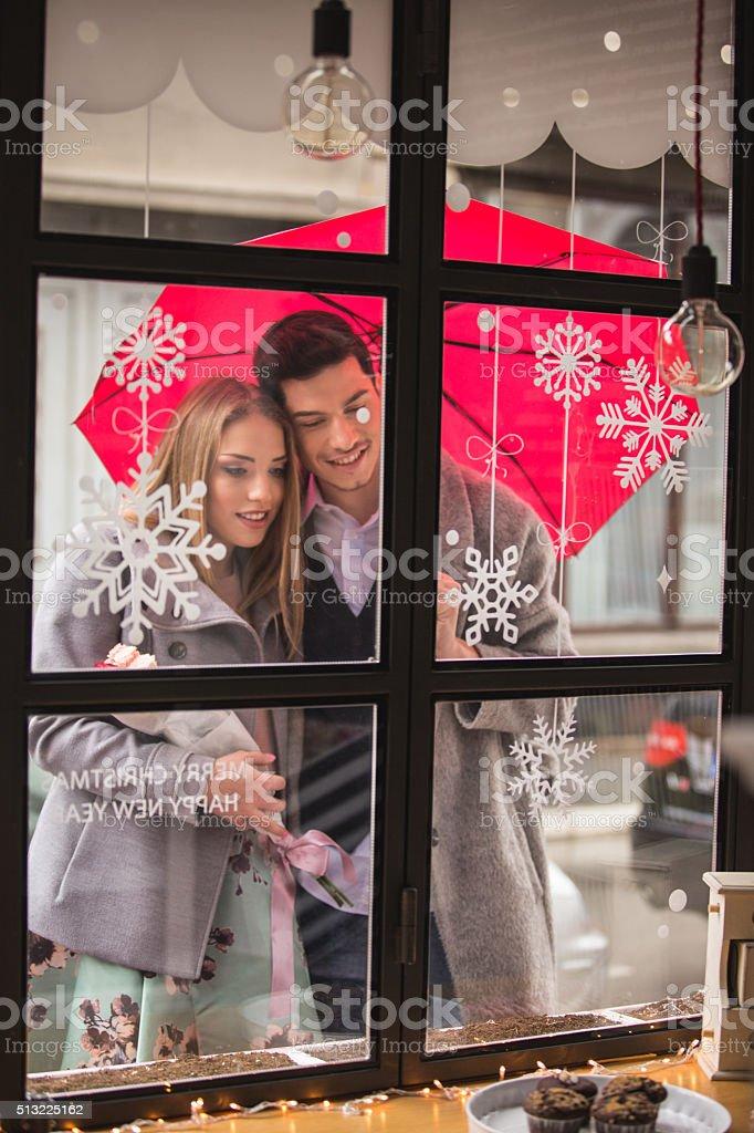 Couple looking into cake shop window stock photo