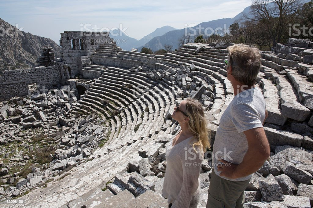 Couple looking out above theatre, ancient Greek ruin stock photo