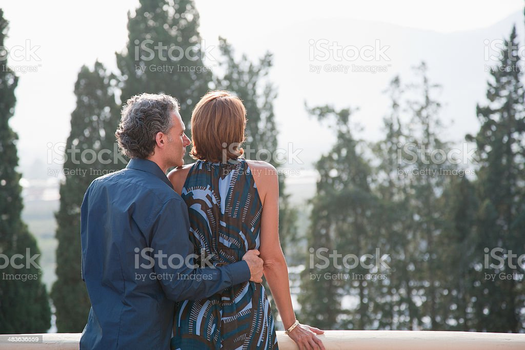Couple looking out  balcony stock photo