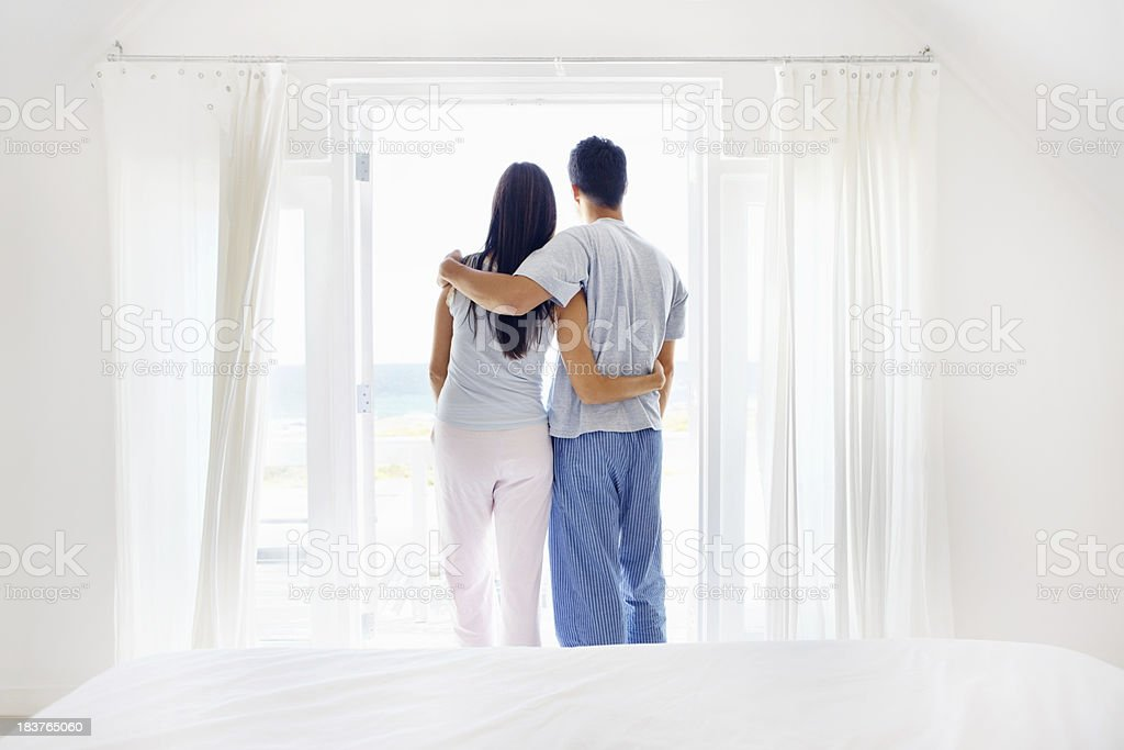 Couple looking out bedroom window royalty-free stock photo