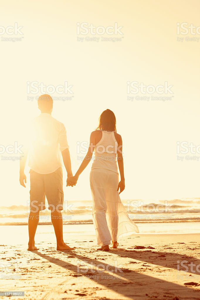 A couple looking out to the sea on a beach holding hands stock photo