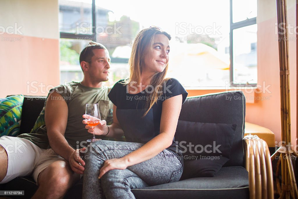Couple looking out window with galss of wine stock photo