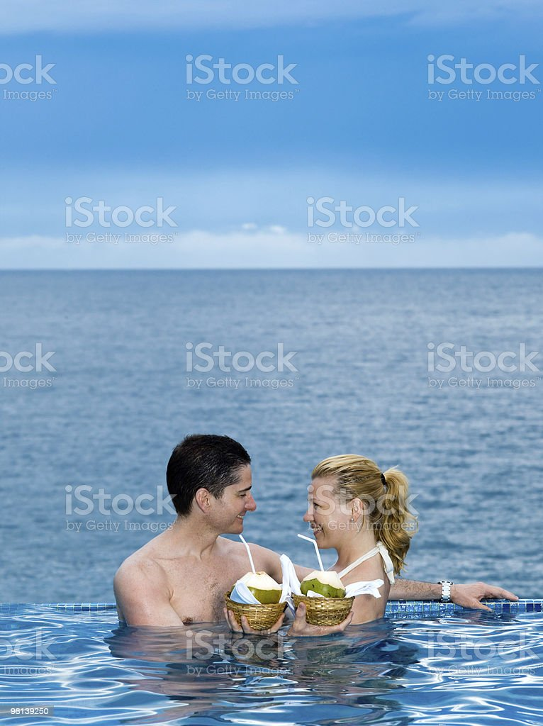 couple lovers swimming pool  seaside drinking coconut milk royalty-free stock photo