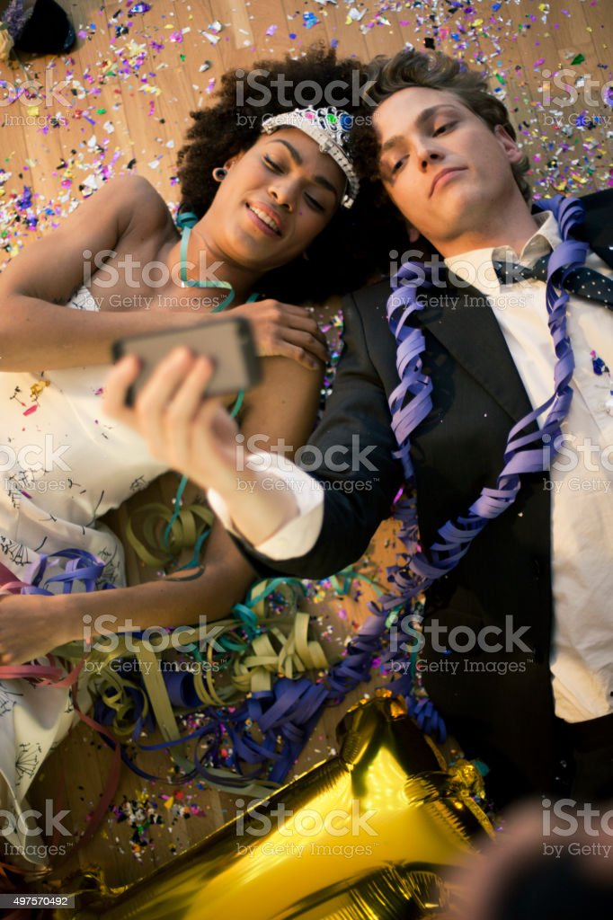 Couple lying down on the floor taking a selfie stock photo