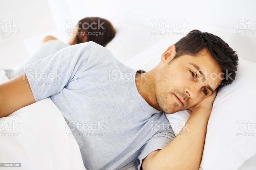 Couple lying in bed awake with their backs to each other royalty-free stock photo