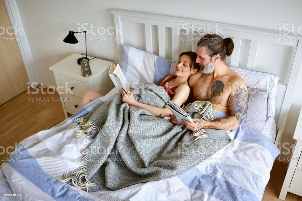 Couple lying in bed reading book and newspaper stock photo