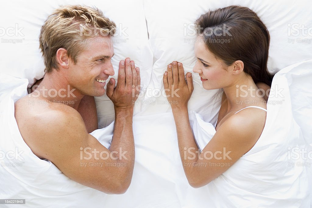 Couple lying in bed smiling royalty-free stock photo