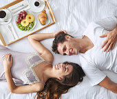Couple lying in bed with breakfast tray