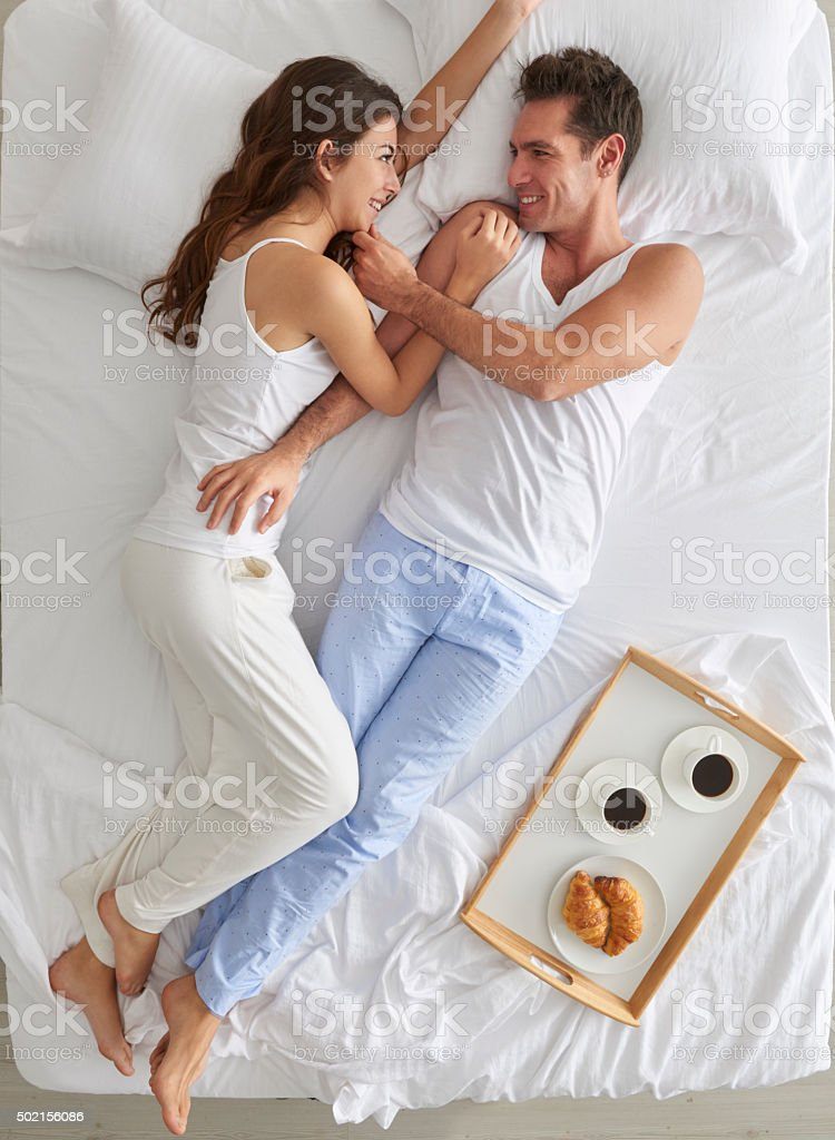 Couple lying in bed with breakfast tray stock photo