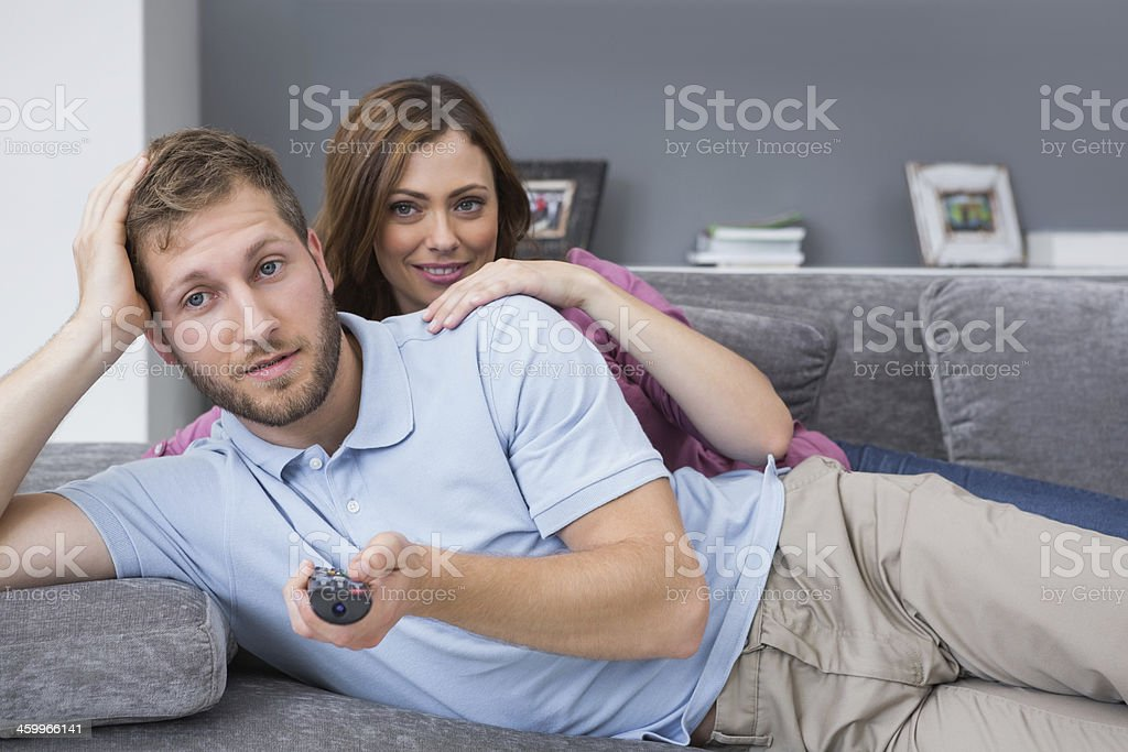 Couple lying on couch watching tv stock photo