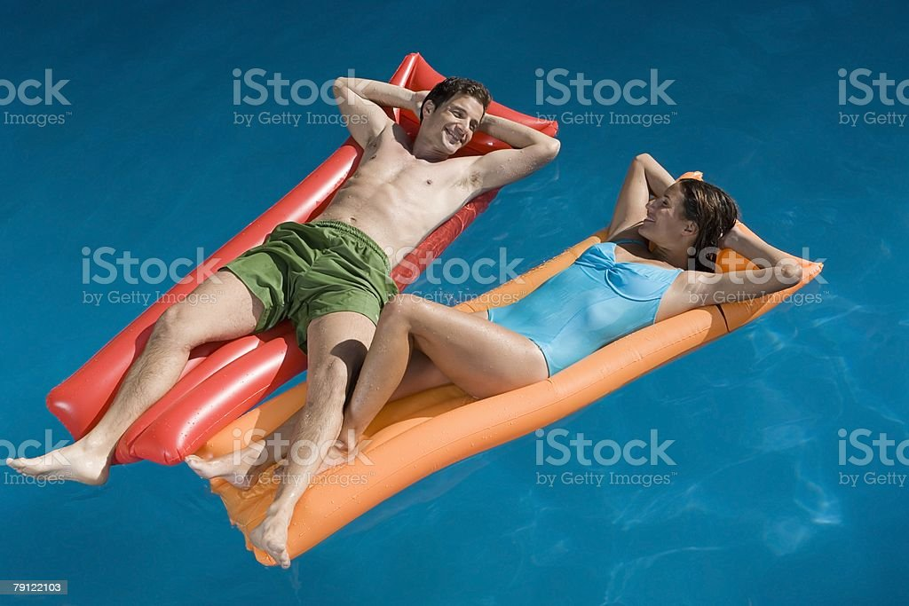 Couple lying on inflatable mattresses royalty-free stock photo