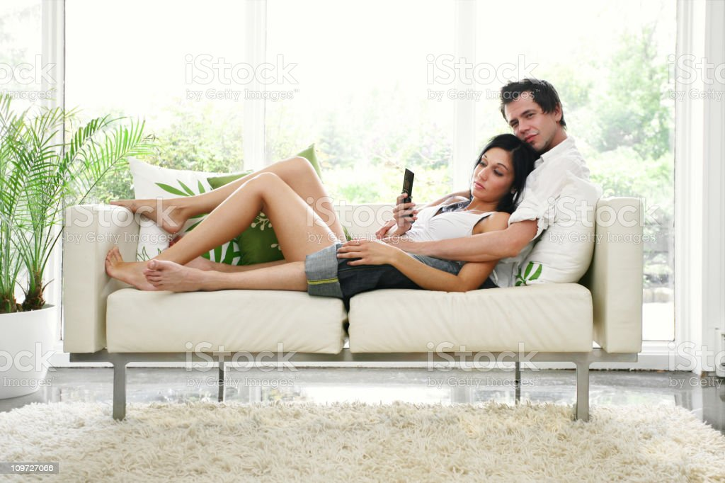 Couple lying on sofa with mobile phone royalty-free stock photo