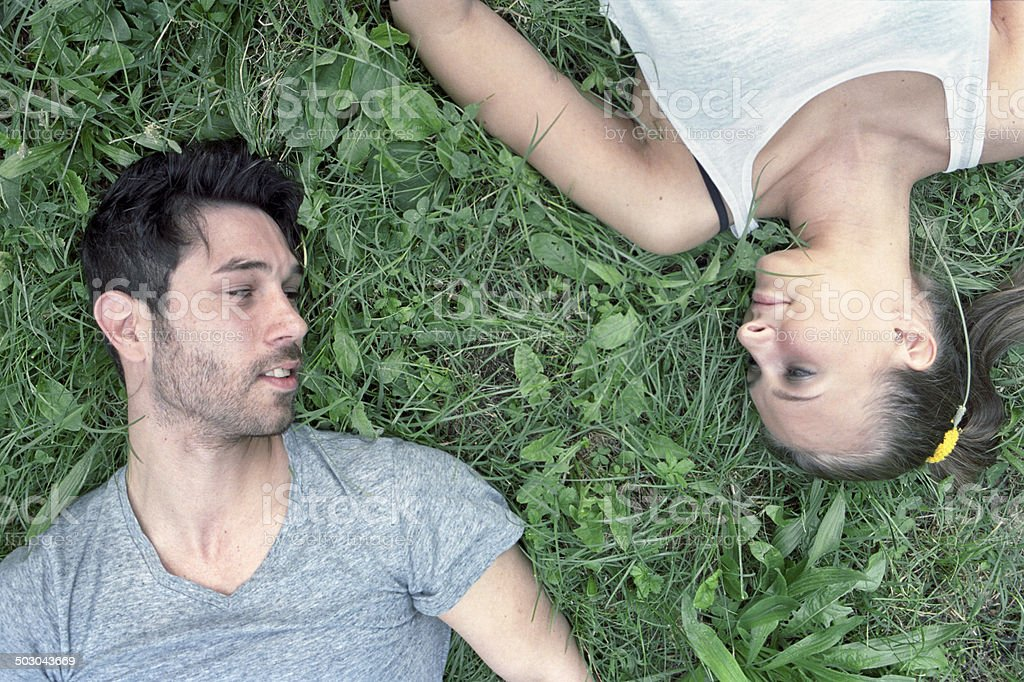 Couple, lying on the grass, looking at each other stock photo