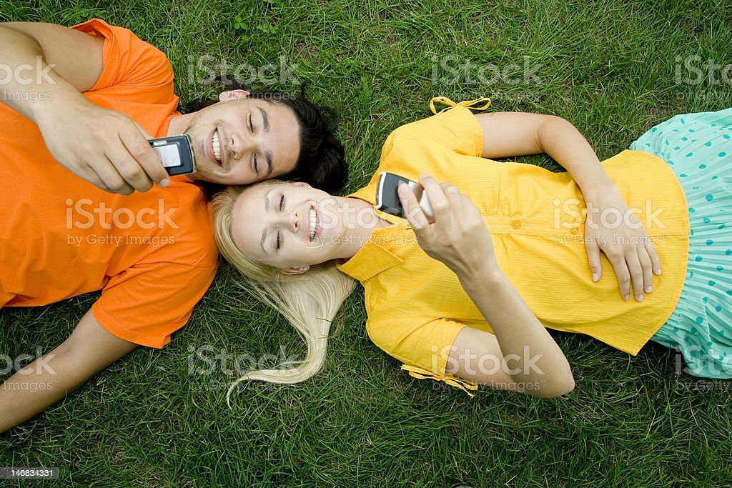 Couple lying on the grass with mobile phones royalty-free stock photo