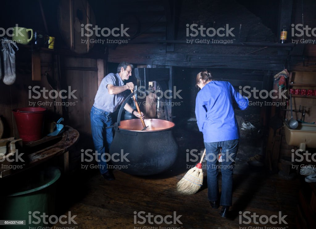 couple make cheese in traditional way in smokey Swiss mountain chalet stock photo