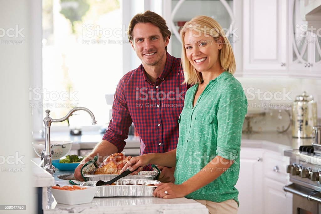 Couple Make Roast Turkey Meal In Kitchen Together stock photo