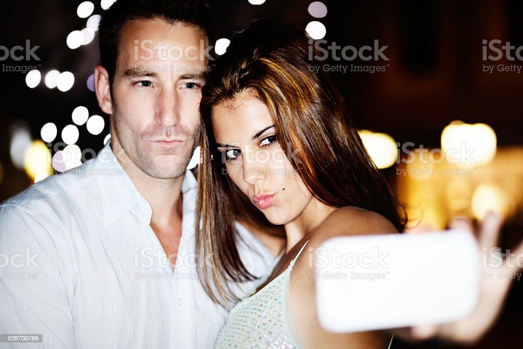 Couple make trout-pout faces, posing for Selfie under twinkling lights stock photo