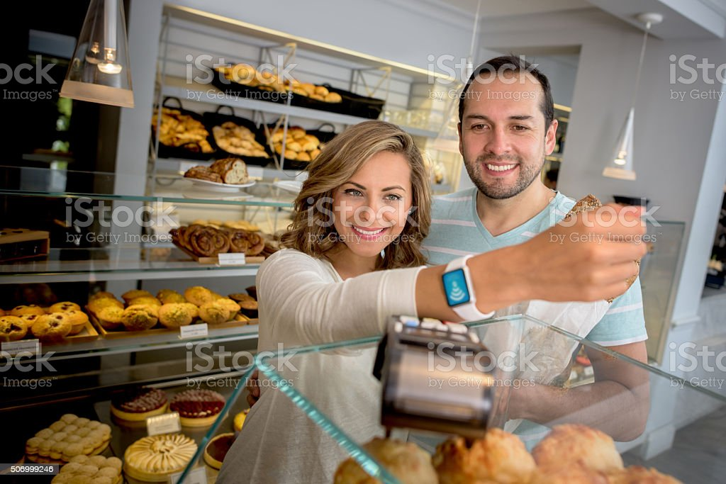 Couple making a contactless payment at the bakery stock photo