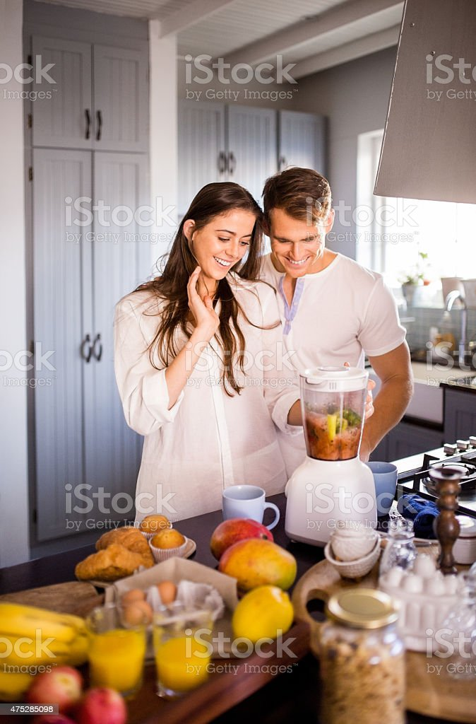 Couple making a healthy juiced breakfast together stock photo