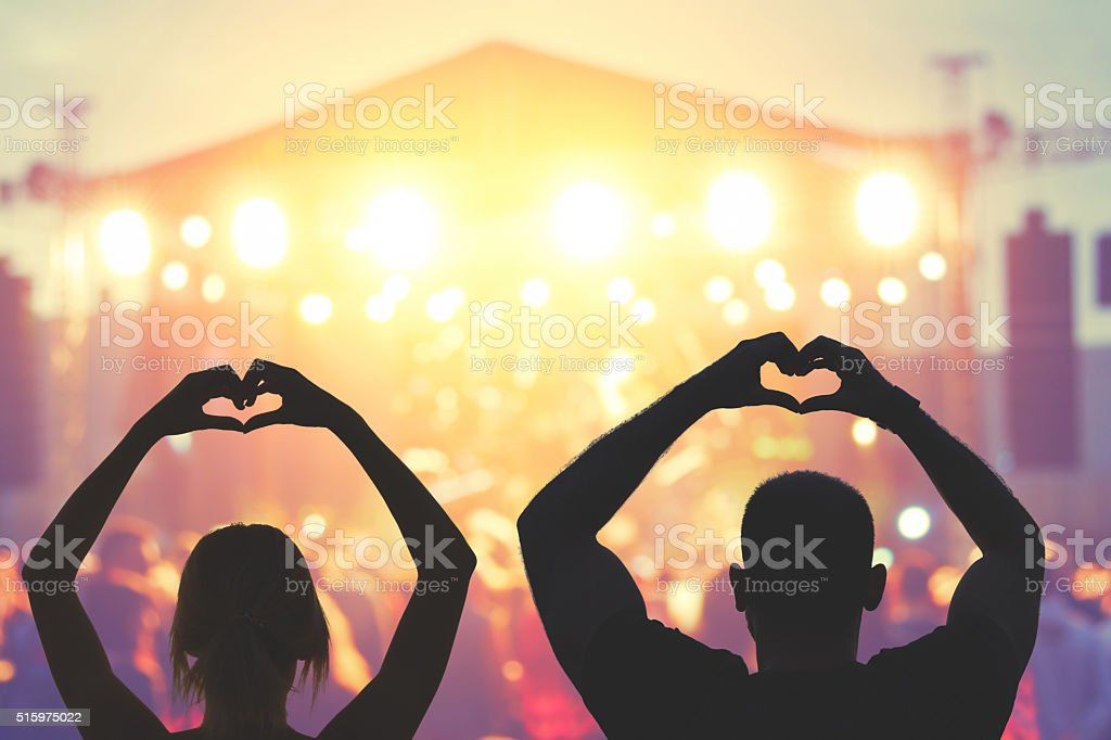 couple making a heart-shape symbol for their favourite band. stock photo