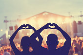 Couple making a heart-shape symbol for their favourite band.