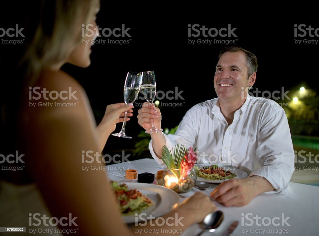 Couple making a toast at a romantic dinner stock photo