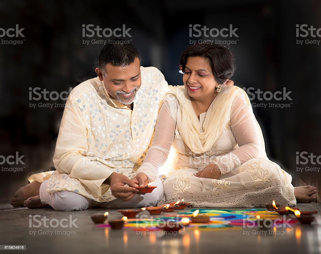 Couple making Rangoli, decorating with Oil lamps for Diwali stock photo