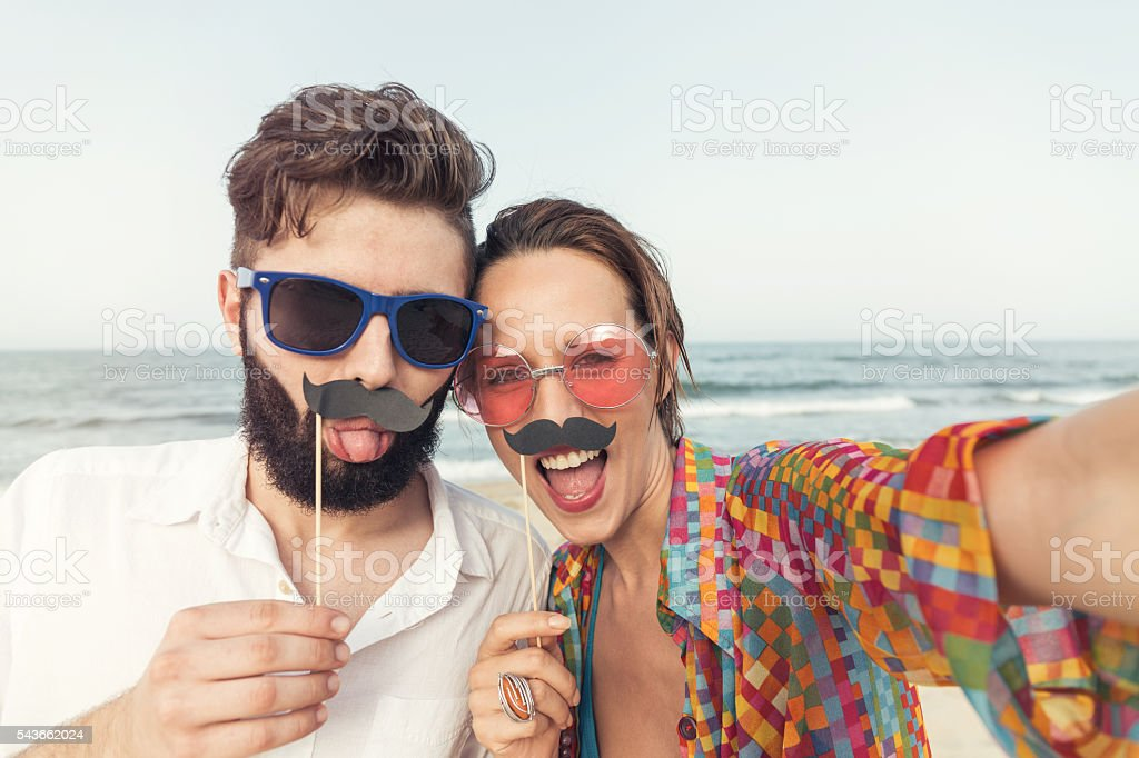 Couple making selfie on the beach with fake moustaches stock photo
