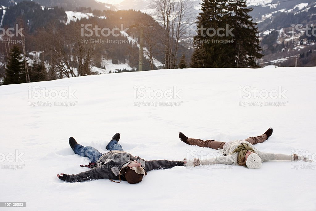Couple making snow angels stock photo