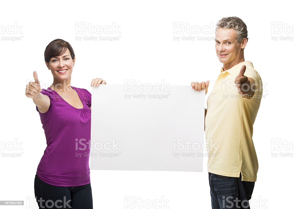 Couple making thumbs up and holding sign royalty-free stock photo