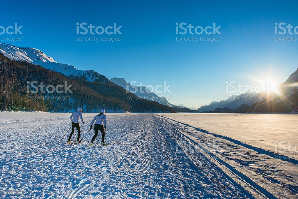 Couple man and woman cross-country skiers with skating technique stock photo