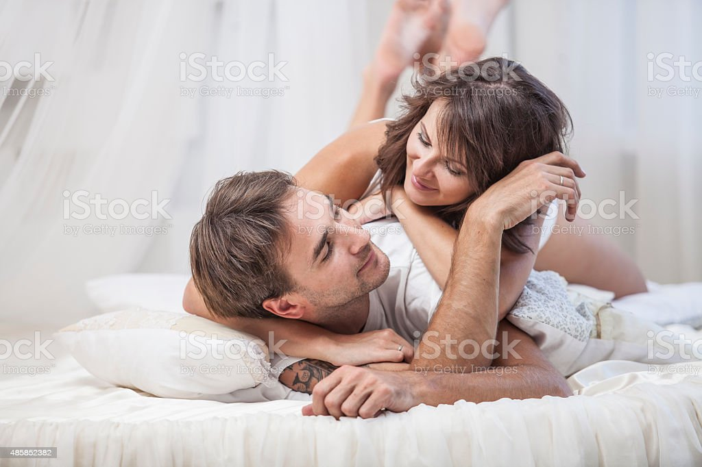couple man and woman lay cuddling on the bed stock photo 485852382 istock. Black Bedroom Furniture Sets. Home Design Ideas